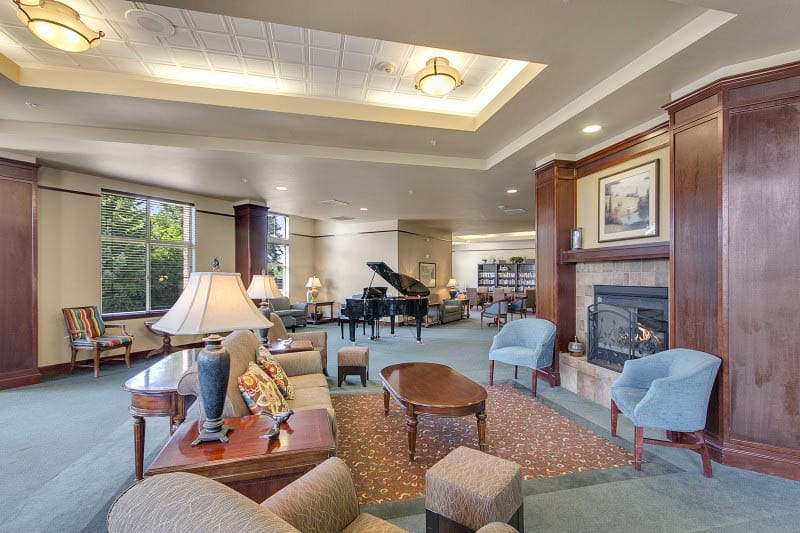 Lounge area with fireplace at Merrill Gardens at Tacoma in Tacoma, Washington.