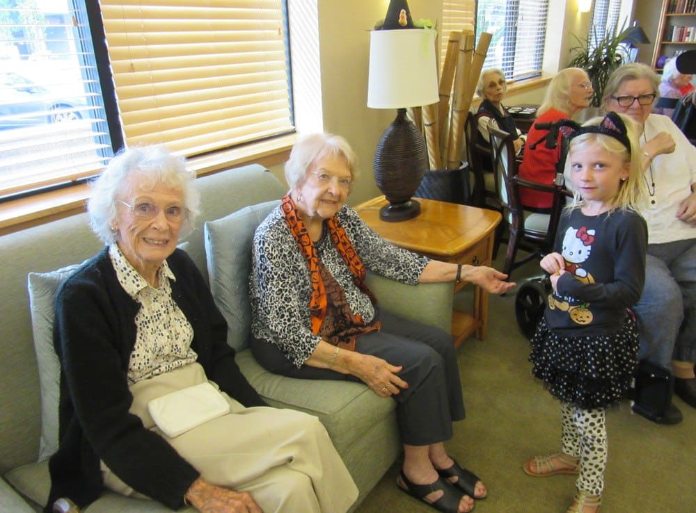 Residents visiting with children at Merrill Gardens at Bankers Hill in San Diego