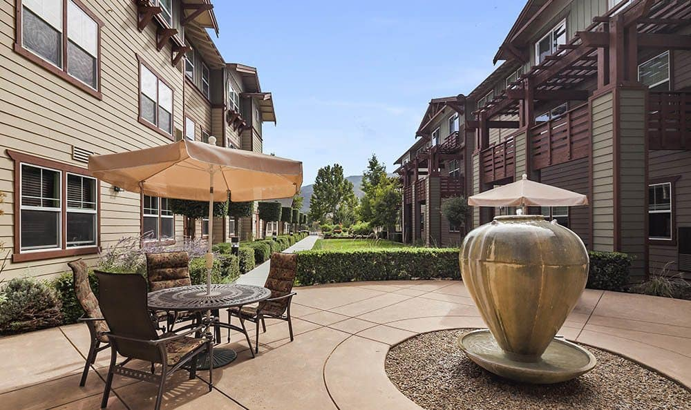 Resident patio with water feature at Merrill Gardens at Gilroy in Gilroy, California.