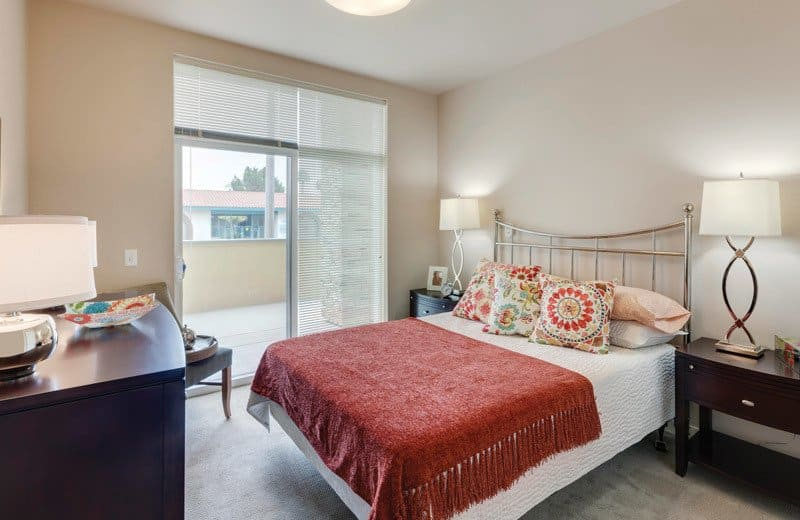 Large resident bedroom at Merrill Gardens at Huntington Beach in Huntington Beach, California.