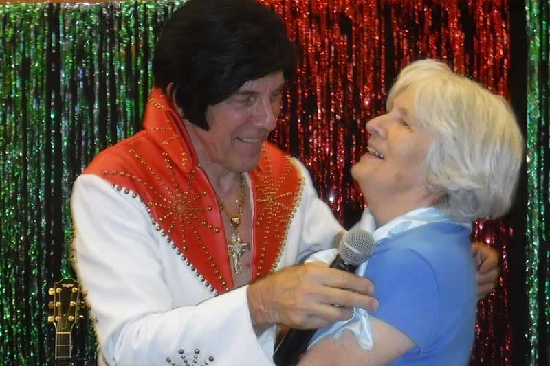 Residents laughing with Elvis at a party at The Groves, A Merrill Gardens Community in Goodyear, Arizona.