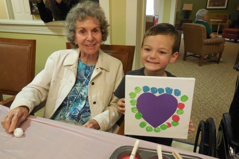 Resident and child make Valentines at The Groves, A Merrill Gardens Community in AZ