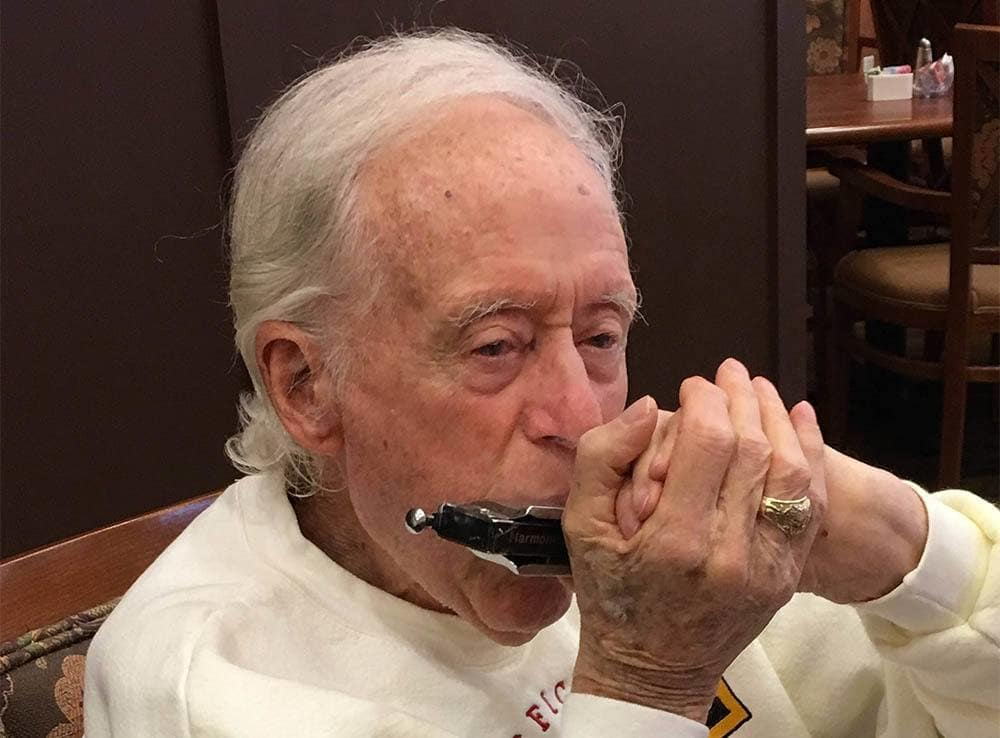 Resident Playing Harmonica at Happy Hour at The Pines, A Merrill Gardens Community in Rocklin