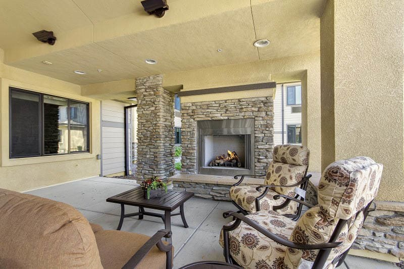 Lounge with fireplace at The Pines, A Merrill Gardens Community in Rocklin, CA