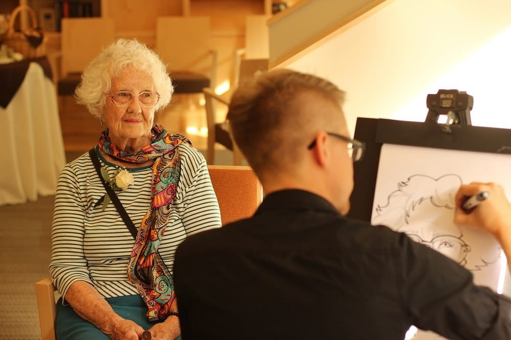 Artist drawing a resident at Merrill Gardens at Ballard in Seattle, Washington.