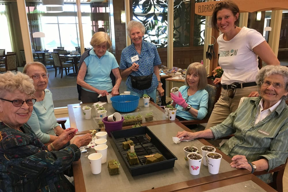 Residents enjoying planting seeds at Merrill Gardens at Burien