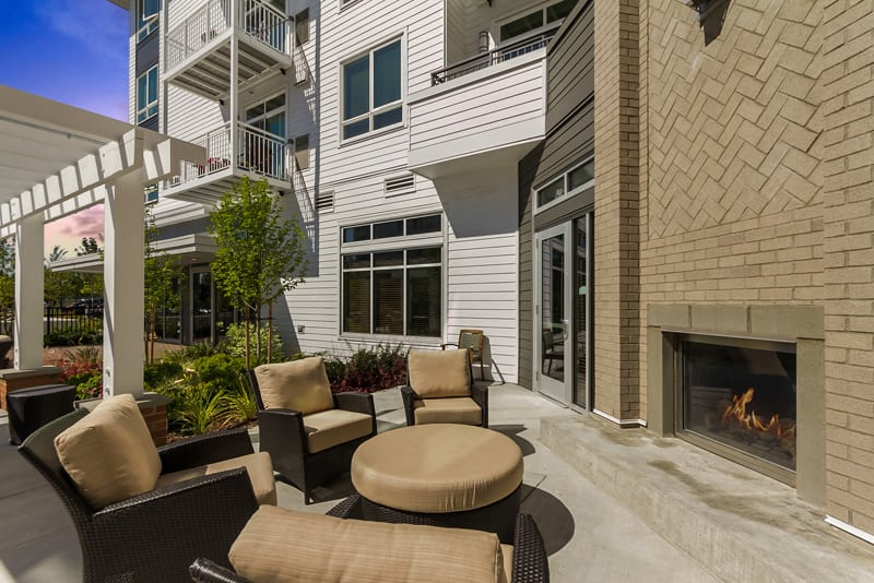 Lounge by the outdoor fireplace at senior living at Merrill Gardens at Burien