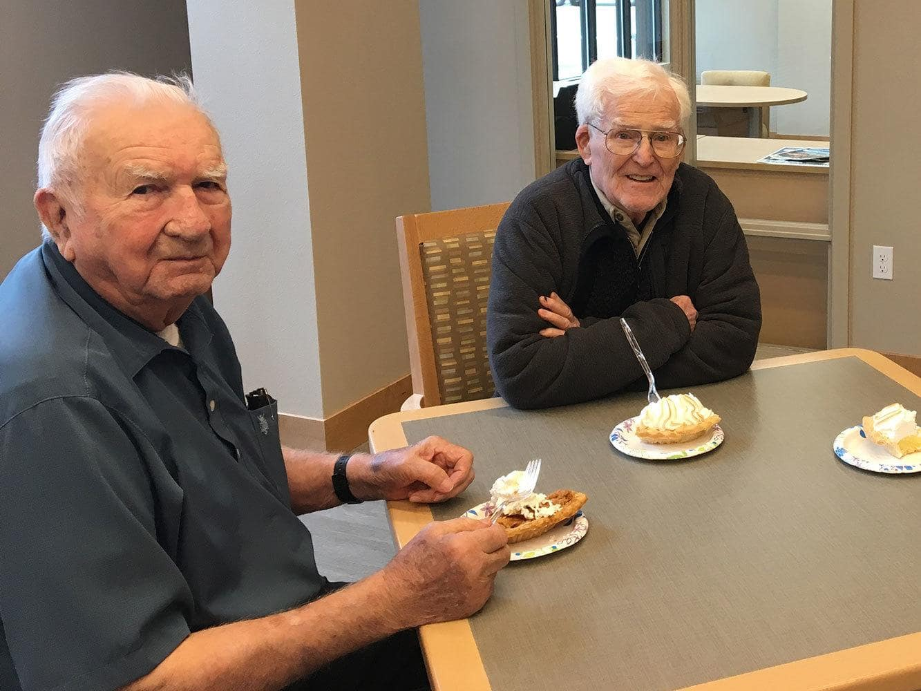 Men enjoying pie together at Auburn