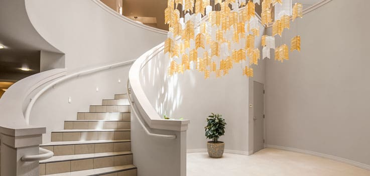 Staircase with chandelier artwork at our senior living community in Monterey, CA