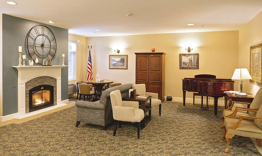Beautiful living room with a fireplace  at King's Manor Senior Living Community