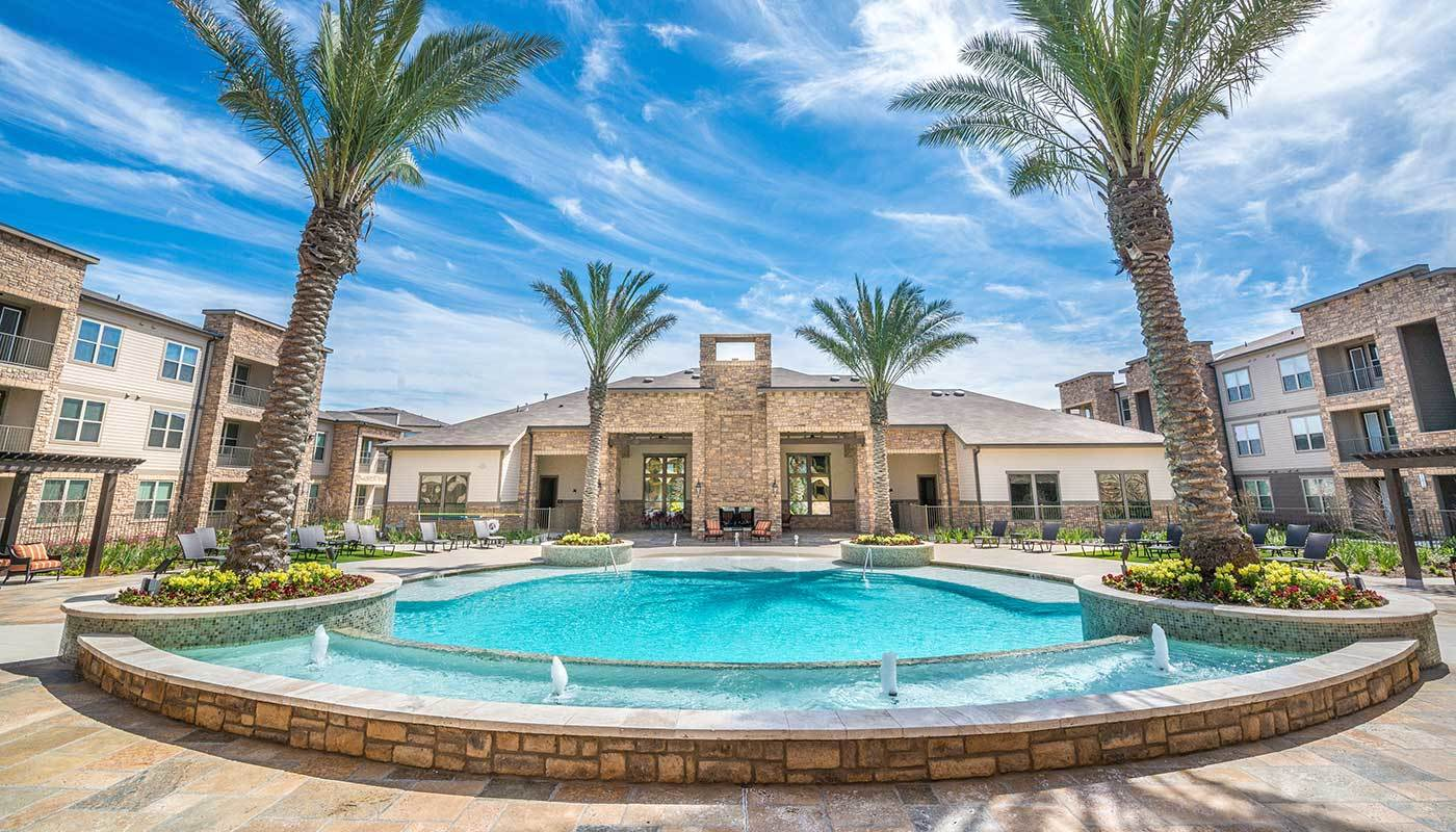 Direct view of the gorgeous clubhouse at The Abbey at Spring Town Center from across the swimming pool