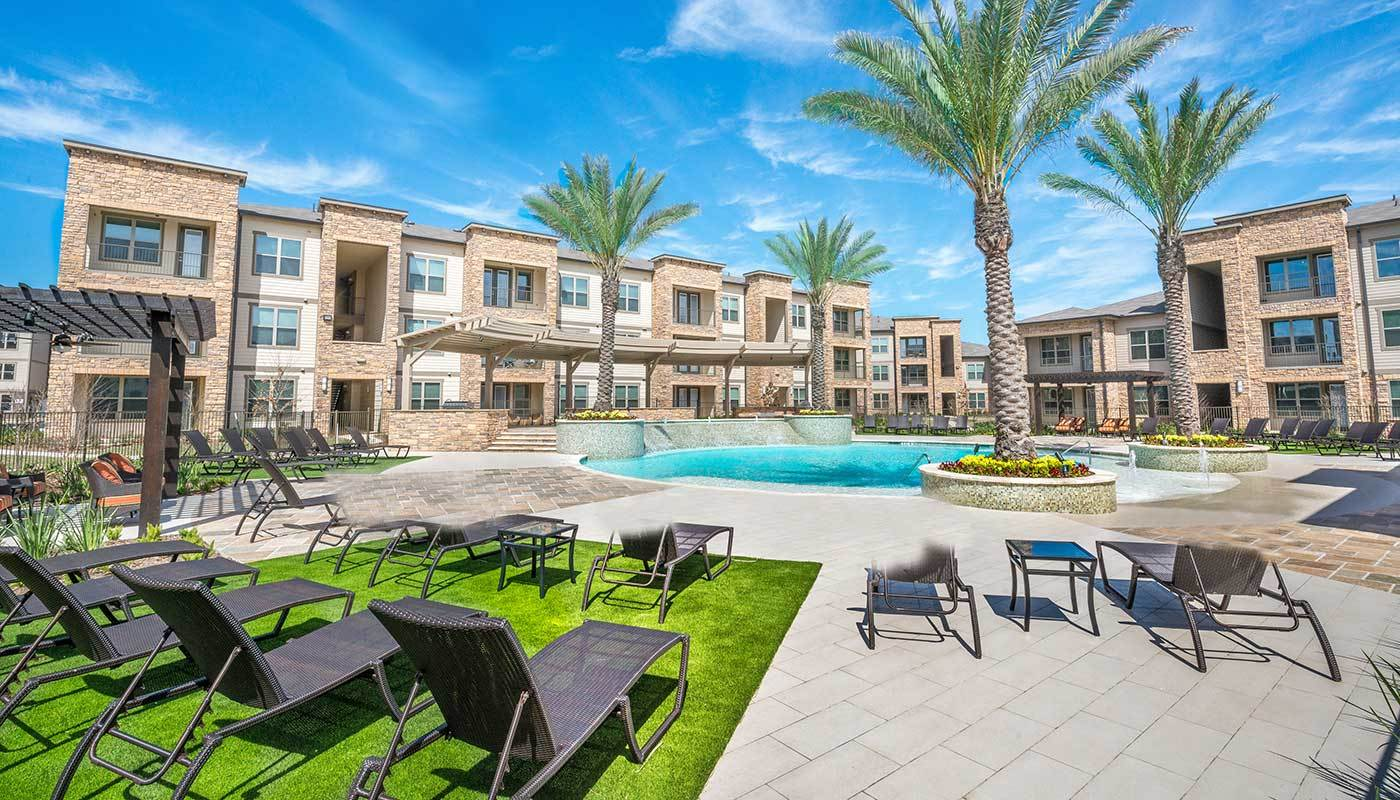 Plenty of comfortable seating for everyone poolside at The Abbey at Spring Town Center in Spring