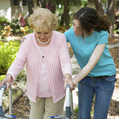 Caretaker helping resident walk at Pecan Ridge Memory Care in Austin