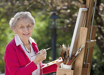 Woman painting at Pecan Ridge Memory Care in Austin
