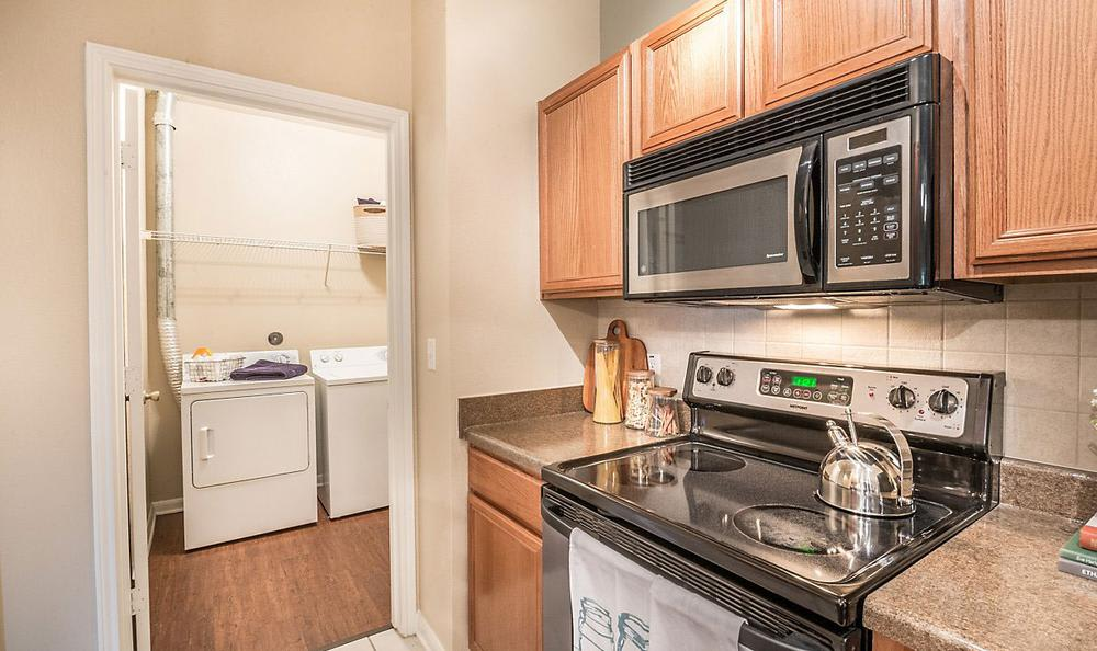 Kitchen And Laundry Room at Avana Stonebriar Apartments in The Colony, TX