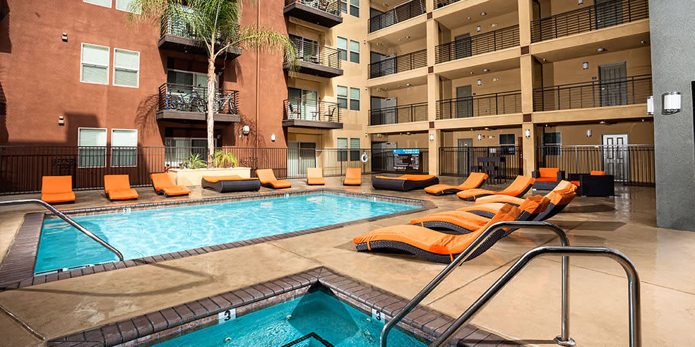 Swimming pool with chairs at Avana North Hollywood Apartments in North Hollywood, CA