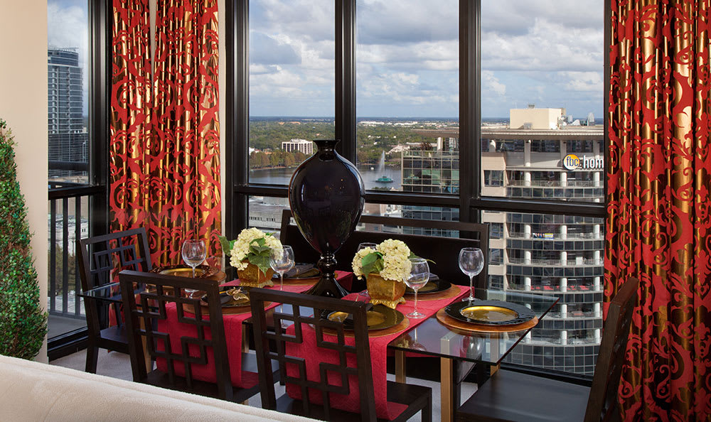 Well-decorated dining area in 55 West Apartments model apartment overlooking the Orlando skyline