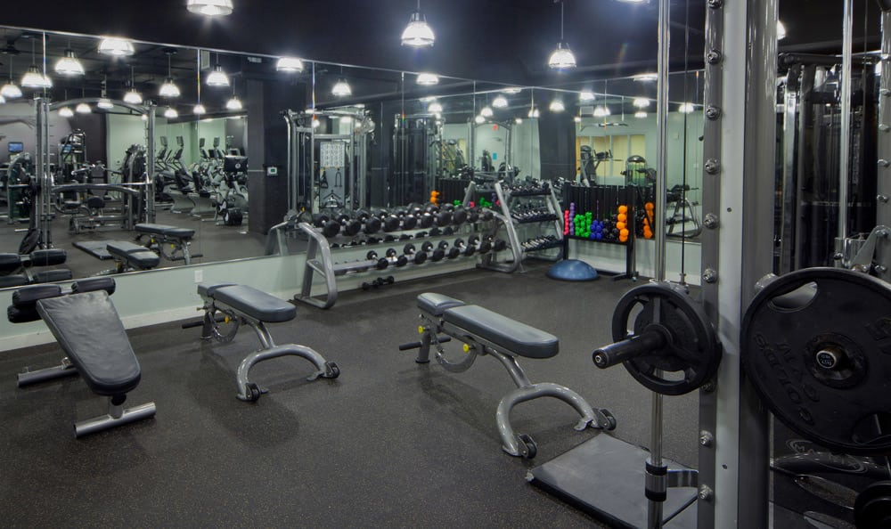 The fully equipped fitness center at 55 West Apartments has free weights and more