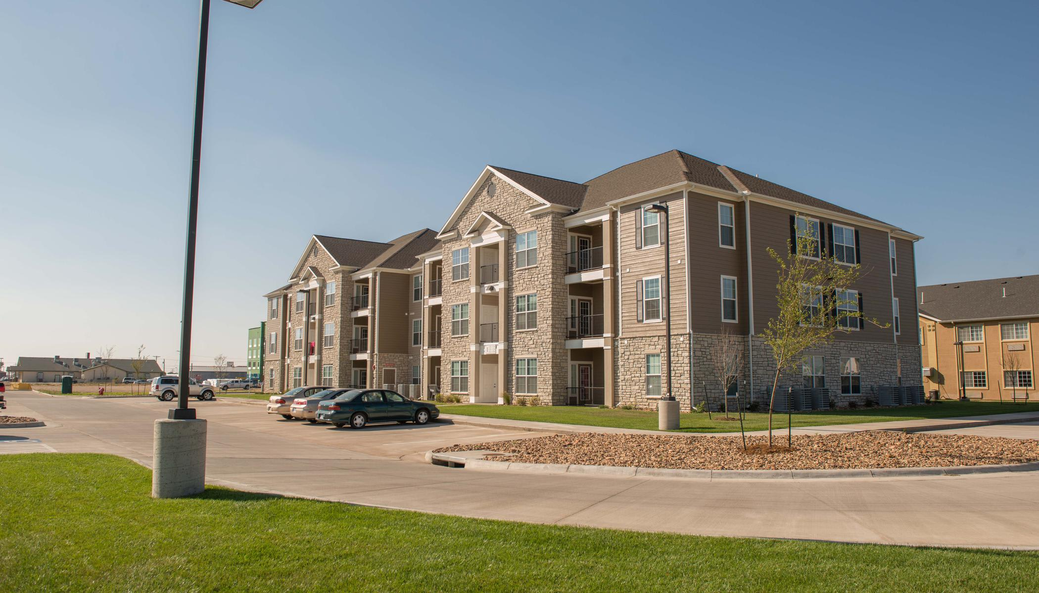 Apartments with parking lot at The Reserves at Trail Ridge in Great Bend, KS