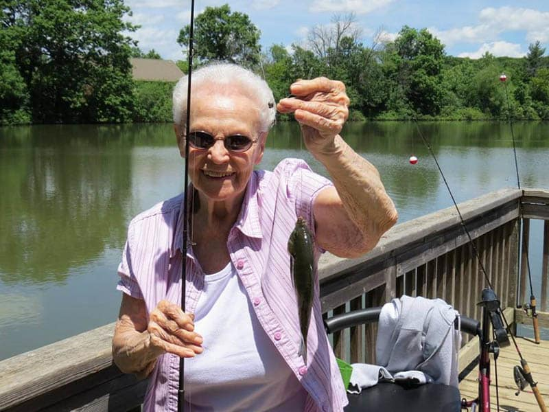 Senior living resident from Pathway to Living fishing at the lake