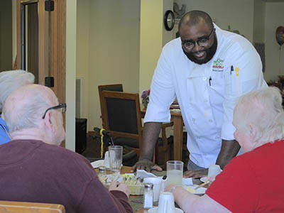 Chef serving residents food at Age Well Centre for Life Enrichment