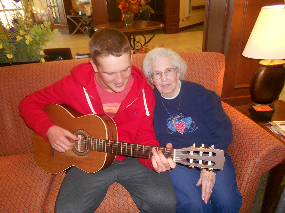 Young man playing guitar with a resident at Oak Hill Supportive Living Community