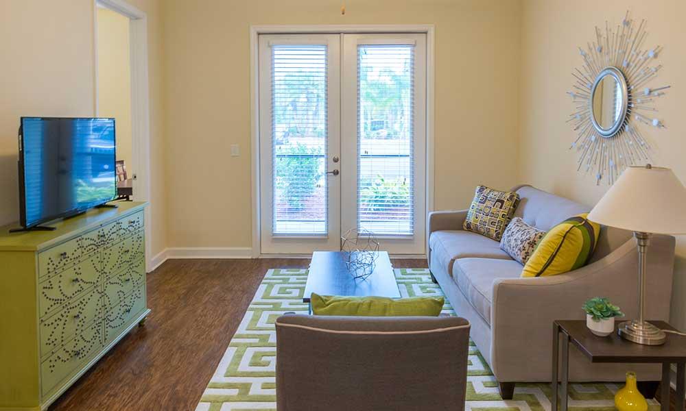 Open floor plan living room with large window doors at Alaqua in Jacksonville, FL