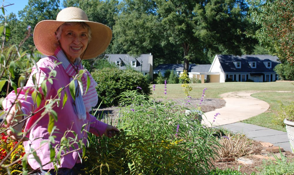 Martha in garden with homes in background at The Clinton Presbyterian Community