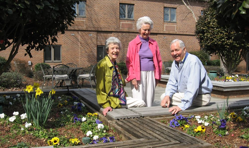 three residents in courtyard garden at The Columbia Presbyterian Community in Lexington, SC