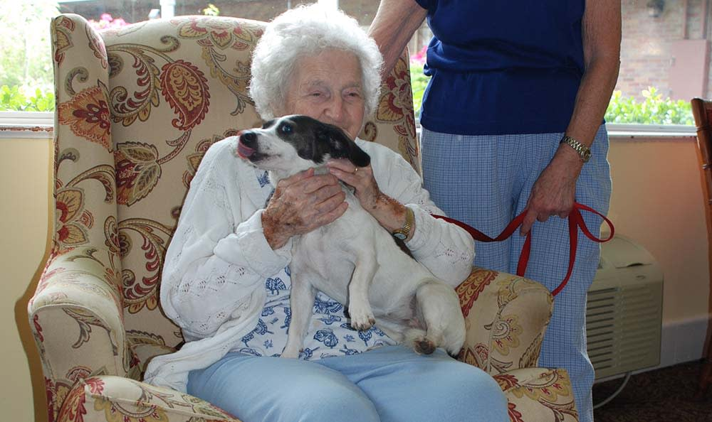 A happy resident and her dog living at The Village at Summerville.
