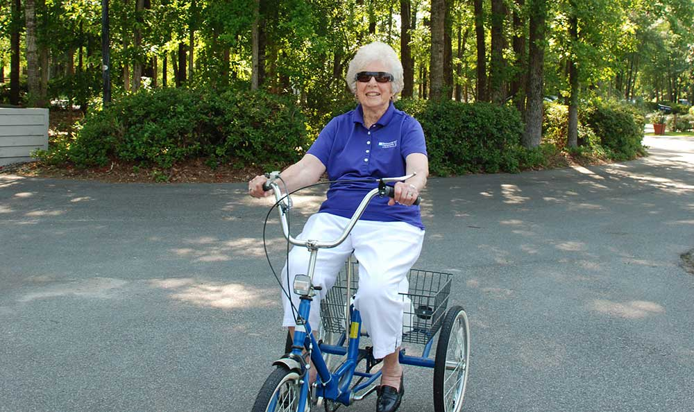 A resident enjoys her tricycle ride around The Village at Summerville.