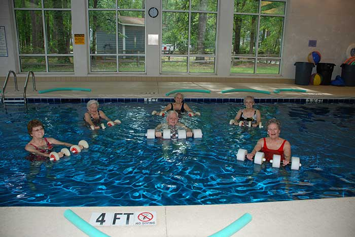 Residents at The Village at Summerville engage in a pool party together.