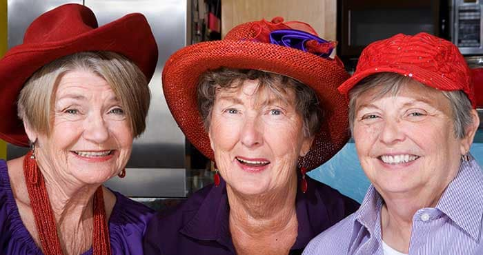 Three happy ladies in their red and glamorous hats at The Foothills Presbyterian Community