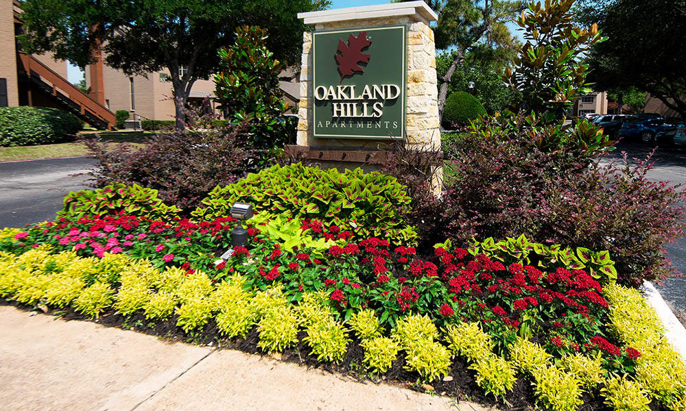 Exterior sign and garden at Oakland Hills in Fort Worth, TX