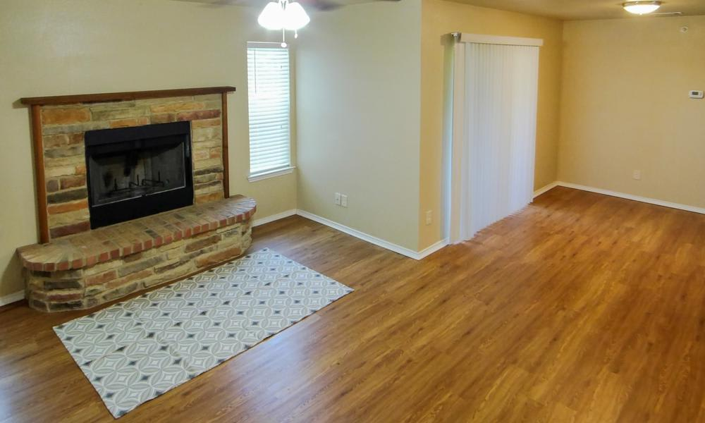Tuscany Apartments offers a living room with chimney in Fort Worth, TX