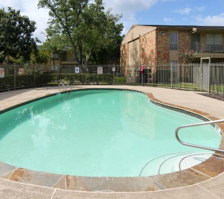 A swimming pool that is great for entertaining at Newport Oaks Apartments in Alvin, TX