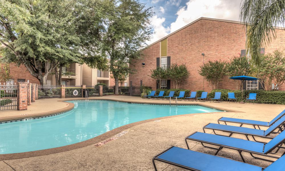 Pool Surrounded By Pool Chairs at Verano Apartments in Houston, TX