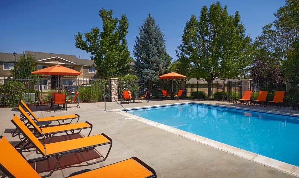sparkling Pool with lounge chairs At Crossroads at City Center Apartments