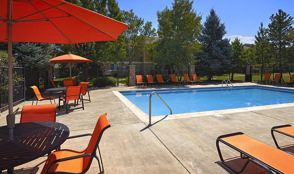 Pool with lounge chairs and umbrellas At Crossroads at City Center Apartments