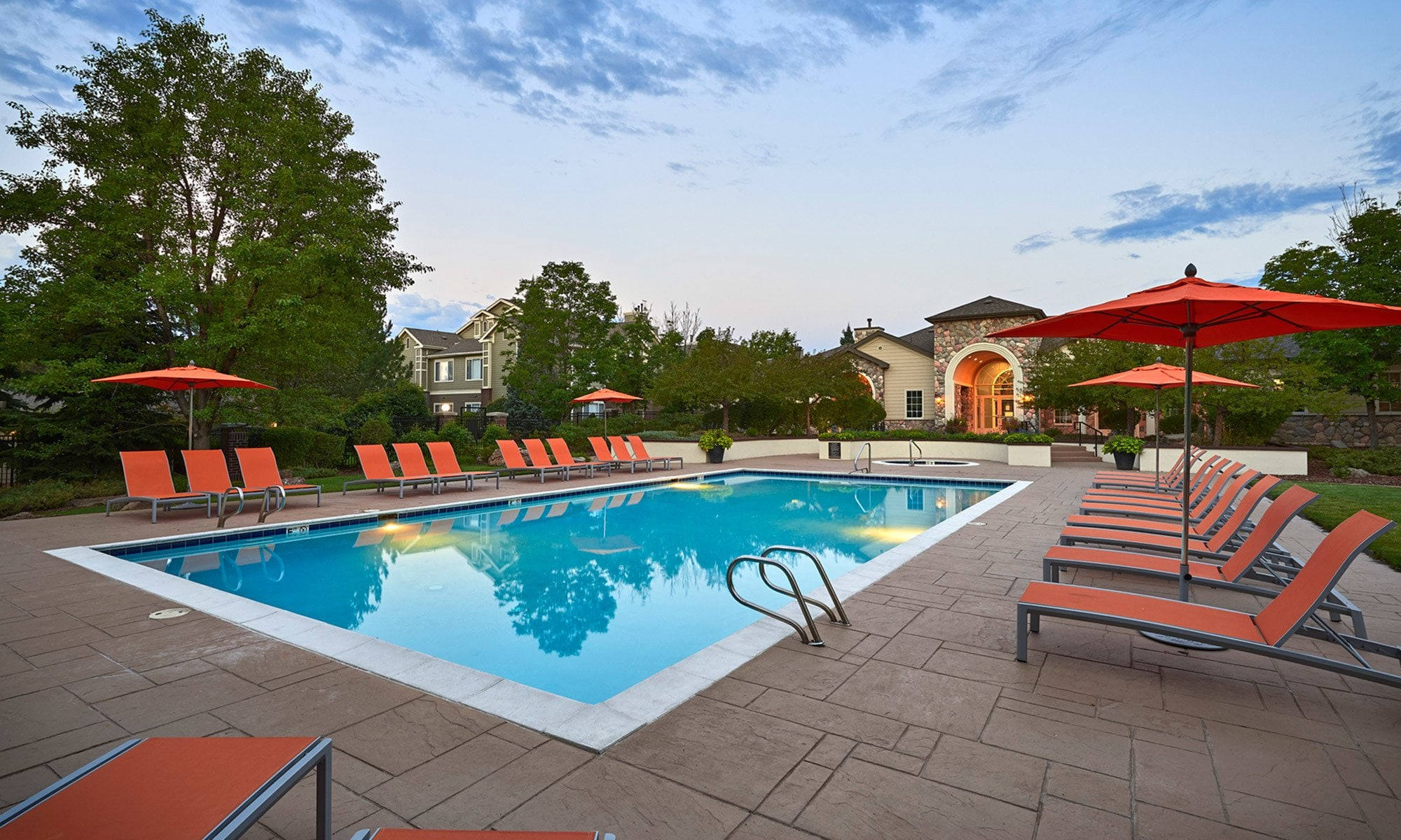 Sunset pool view with lounge chairs in Denver, CO