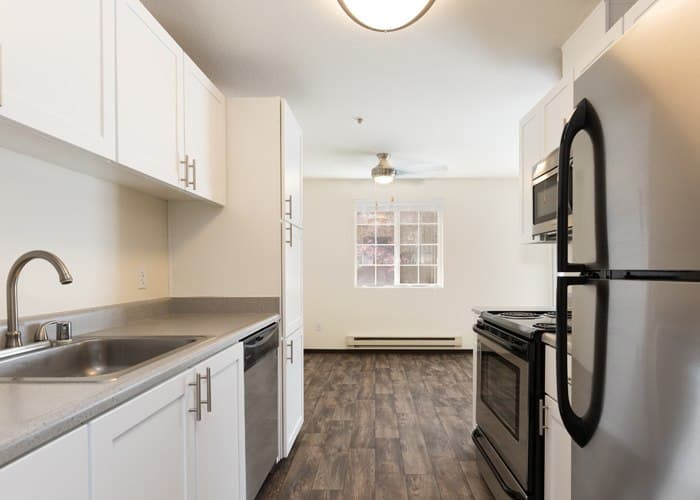 Renovated white Kitchen with stainless steel appliances and Living Room at Renaissance at 29th Apartments in Vancouver