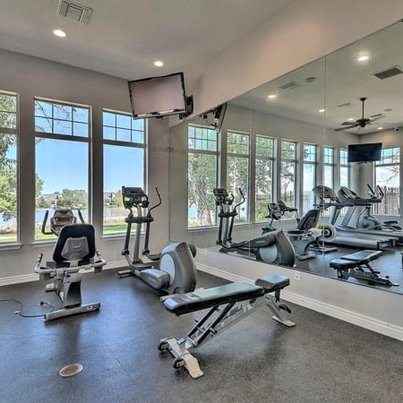 Fully equipped fitness center with large window lake views at Promenade at Hunter's Glen Apartments in Thornton