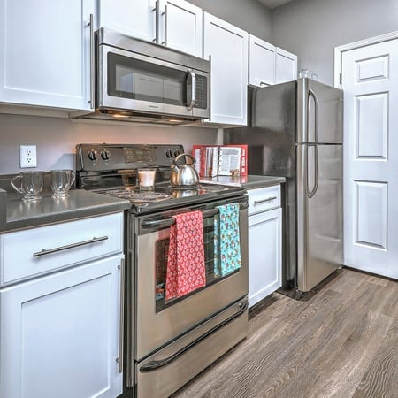 Renovated white spec model kitchen at Promenade at Hunter's Glen Apartments in Thornton