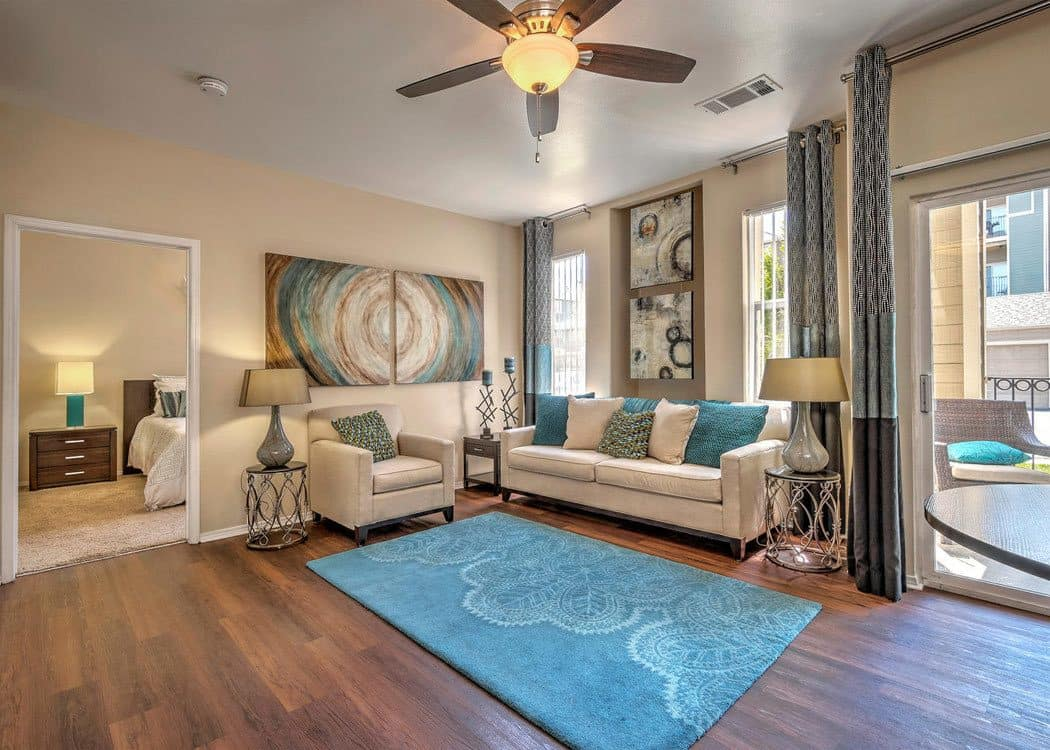 Open concept apartment model living room at Promenade at Hunter's Glen Apartments in Thornton