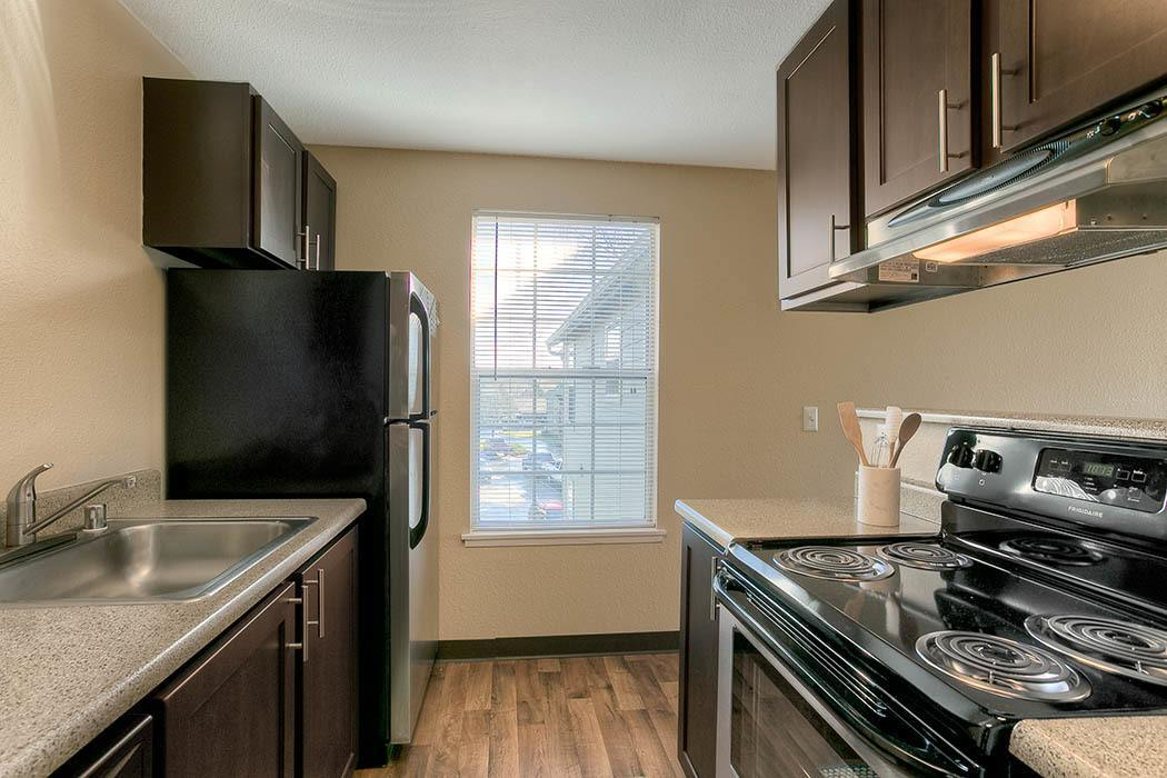 renovated brown kitchen with stainless steel appliances at Waters Edge Apartments in Kent, WA