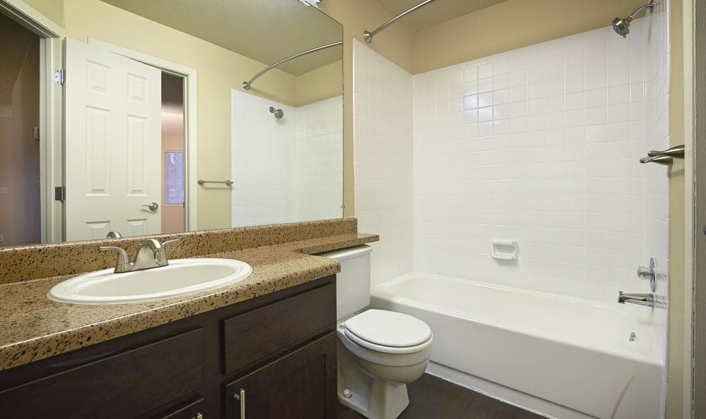 Neat brown renovated bathroom with tub at Bluesky Landing Apartments in Lakewood, CO