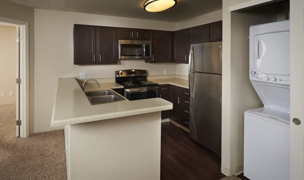 Kitchen fully equipped with washer and dryer at Bluesky Landing Apartments