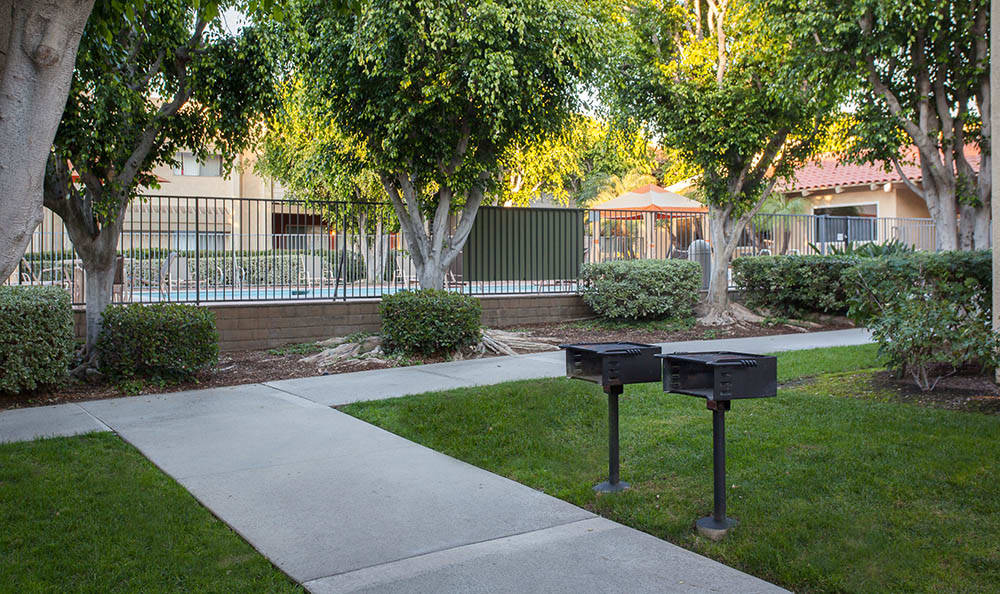 Outdoor Community Area With Grills At Kendallwood Apartments