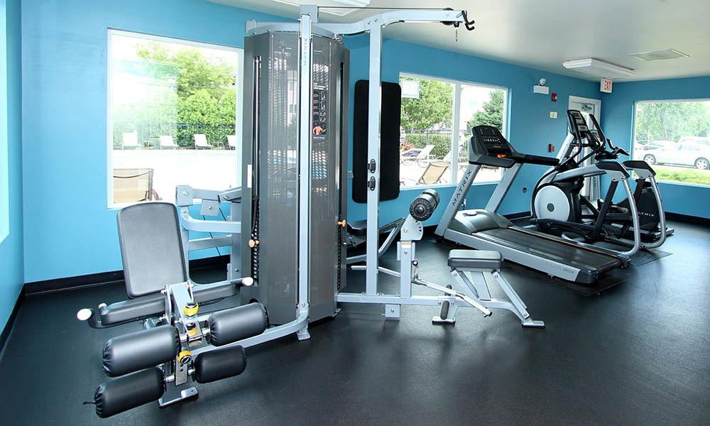 Gym Equipment with large windows looking out to the pool area at West Line Apartments in Hanover Park, Illinois