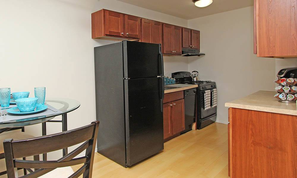 Connected Dining Room And Kitchen with black appliances At West Line Apartments in Hanover Park, Illinois
